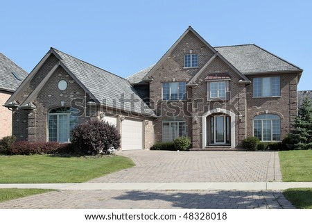 Suburban brick home with arched entry and three car garage
