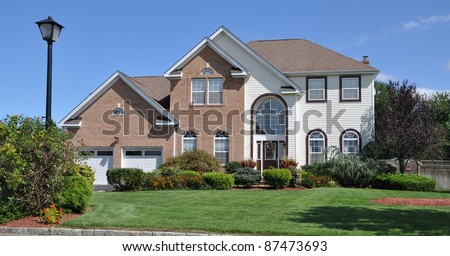 Suburban Brick Siding Two Car Garage Home Landscaped Front Yard in Residential District on Blue Sky Day - stock photo