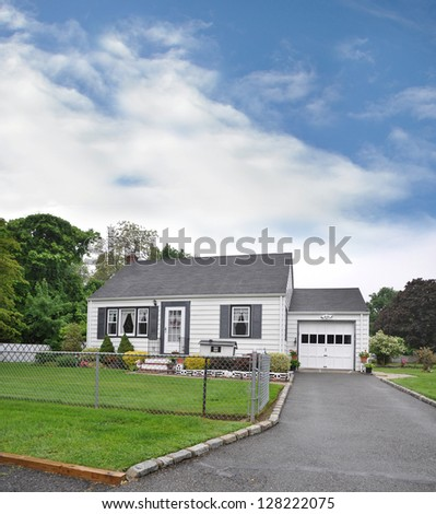 Suburban Bungalow Home Chain link Fence Blacktop Driveway Just After Rain - stock photo