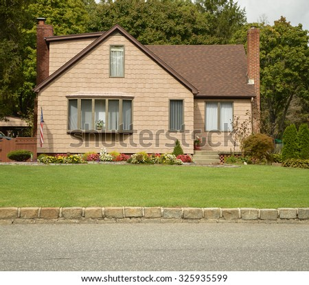 Suburban Bungalow Home Flowers Cobblestone curb  Overcast Sky residential neighborhood USA - stock photo