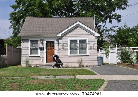 Suburban Bungalow Home with Baby Carriage Parked on Front Yard Lawn Sunny Residential Neighborhood House USA - stock photo