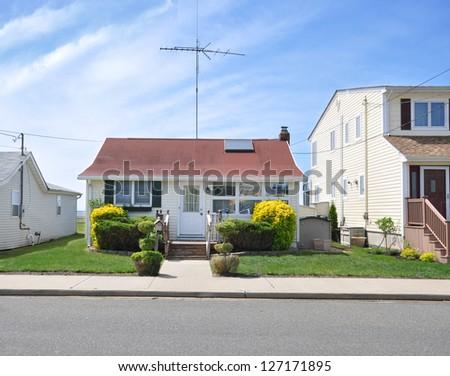 Suburban Bungalow Home with Skylight Window Antenna Blue Sky Clouds - stock photo