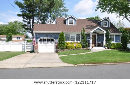 Suburban Cape Cod Style Home Cement Driveway Landscaped American Flag Sunny Day - stock photo