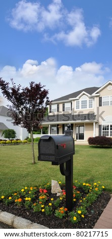 Suburban Closed Black Mailbox with Embossed Envelope Flower Bed Split Level Suburban Home in residential neighborhood - stock photo
