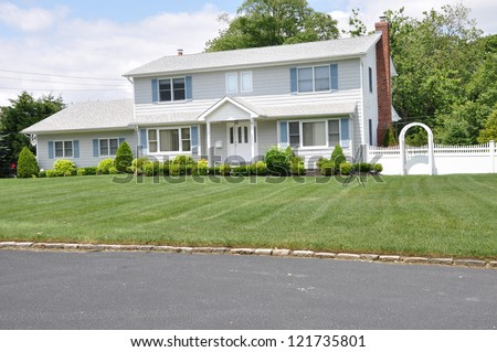 Suburban High Ranch Home landscaped front yard lawn sunny day with clouds - stock photo