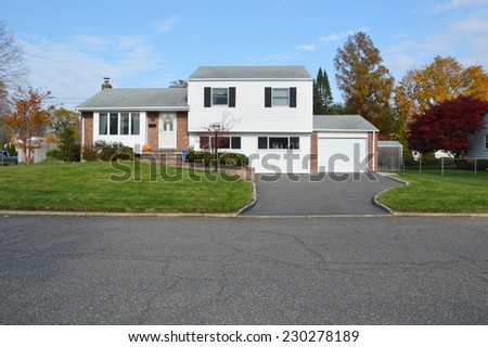 Suburban high ranch style home residential neighborhood fall season blue sky clouds USA - stock photo