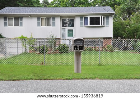 Suburban High Ranch style home with Chain link fence curbside Mailbox residential neighborhood USA - stock photo