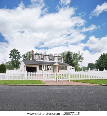 Suburban High Ranch White Picket Fence Brick Driveway Residential Neighborhood Street Blue Sky Clouds - stock photo