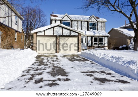 Suburban Home Covered with Snow on a Sunny Day - stock photo