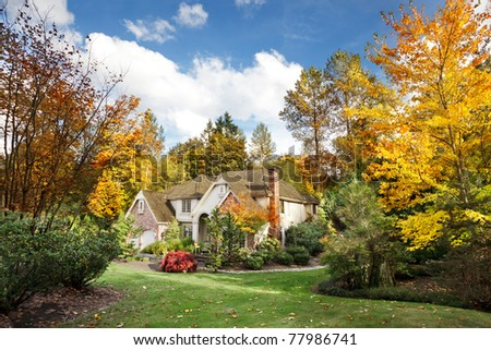 Suburban home in Autumn sunshine as the leaves turn orange & yellow - stock photo