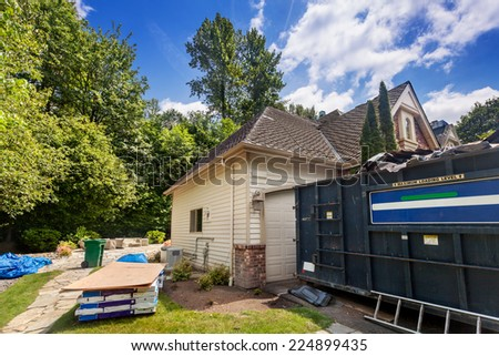 Suburban home in the middle of a re-roofing project, with new shingles and plywood waiting to be installed and dumpster to contain the debris - stock photo