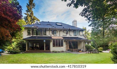 Suburban home in the middle of roof replacement. Old cedar shakes removed. - stock photo