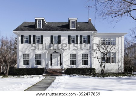 Suburban home in winter with black shutters