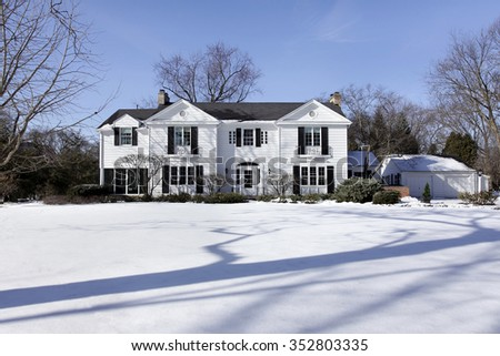 Suburban home in winter with detached garage - stock photo