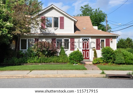 Suburban Home on middle class residential neighborhood street with gutter sunny blue sky day - stock photo