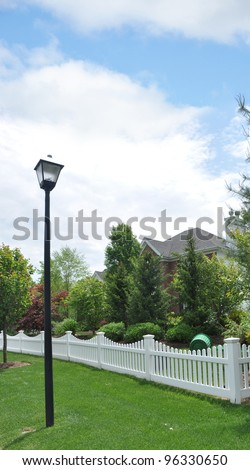 Suburban Home Picket Fence Lamp post grassy curb area