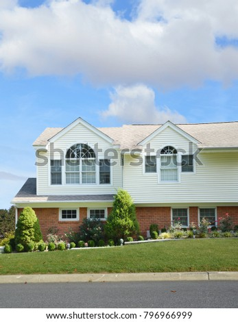 Suburban home with arch windows blue sky clouds USA