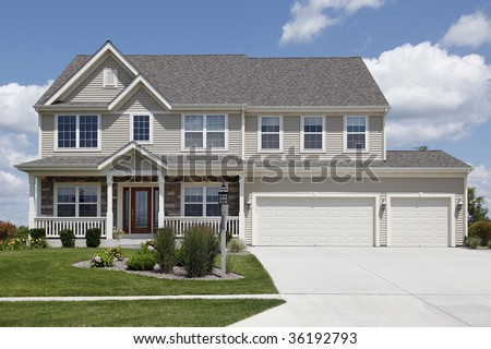 Suburban home with beige siding and double garage - stock photo