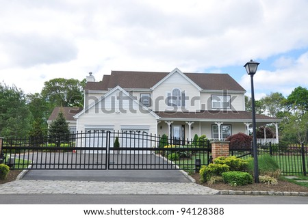 Suburban Home with Black Rod Iron Fence in Residential District Neighborhood - stock photo