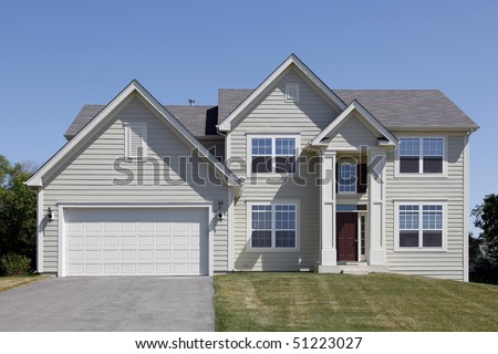 Suburban home with cream colored siding and arched entry - stock photo