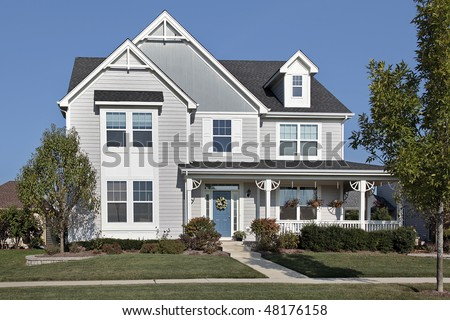 Suburban home with front porch and blue door - stock photo