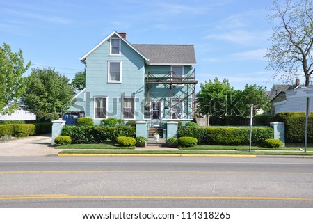 Suburban Home with scaffold equipment for repair work on Gable Style House residential neighborhood sunny blue sky day - stock photo