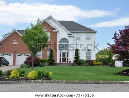 Suburban Home with Small Pesticide Sign on front Lawn in residential neighborhood - stock photo