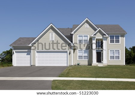 Suburban home with tan siding and arched entry - stock photo