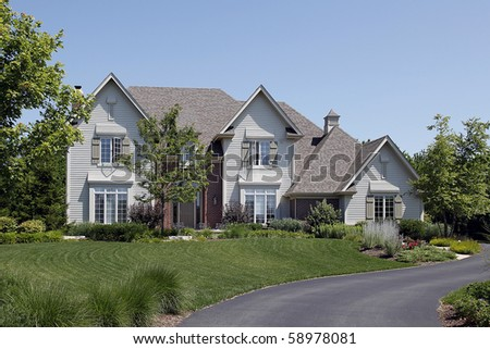 Suburban home with white siding and brick entry