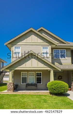 Suburban house facade with green lawn in front and blue sky background