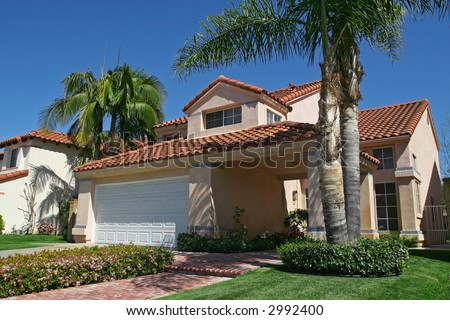 suburban house with palm trees in the front yard - stock photo