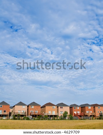 Suburban houses with large sky area - stock photo