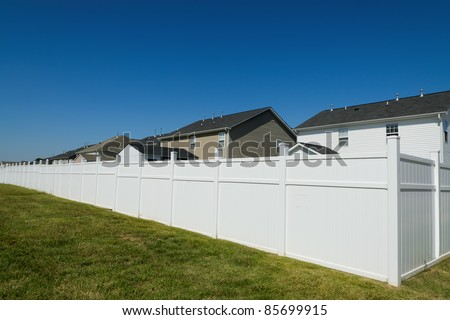 Suburban landscape with a long vinyl fence - stock photo
