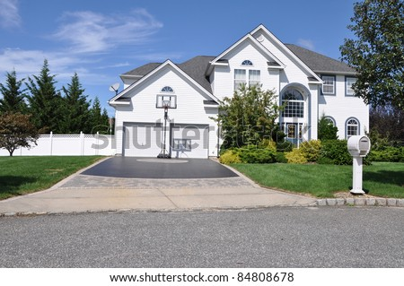 Suburban Luxury Two Story Two Car Garage Home Basketball Hoop Designer Driveway Mailbox Front Yard Sunny Day