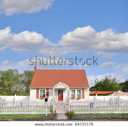 Suburban Middle Class Country Bungalow Cottage Home with White Picket Fence Beautiful Blue Cloudy Sky - stock photo