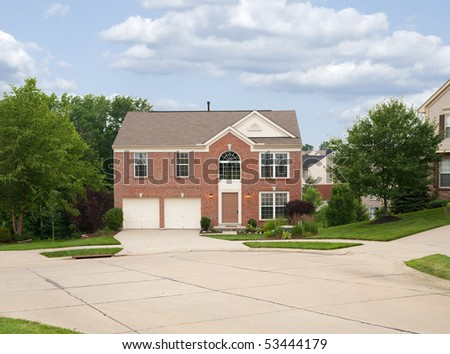 Suburban Neighborhood Brick Home - a spring day in the burbs. - stock photo