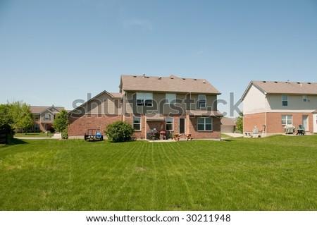 Suburban Neighborhood Brick Home back yards - a spring day in the burbs. - stock photo