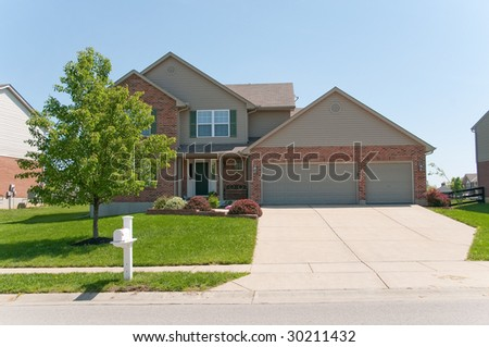 Suburban Neighborhood Brick Homes - a spring day in the burbs. - stock photo