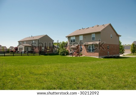 Suburban Neighborhood Brick Homes back yards - a spring day in the burbs. - stock photo
