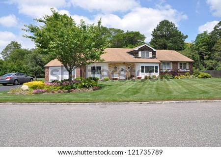 Suburban Ranch Home made with Stone surrounded by plants and flowers in Residential Neighborhood Sunny Blue Sky Day Clouds