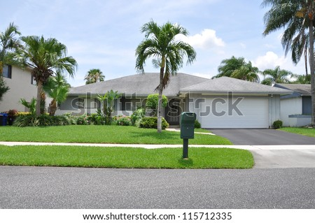 Suburban Ranch Style Home with mailbox on curb in tropical climate residential neighborhood