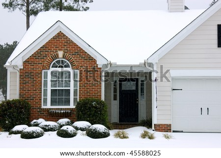 Suburban residential house during winter storm - stock photo
