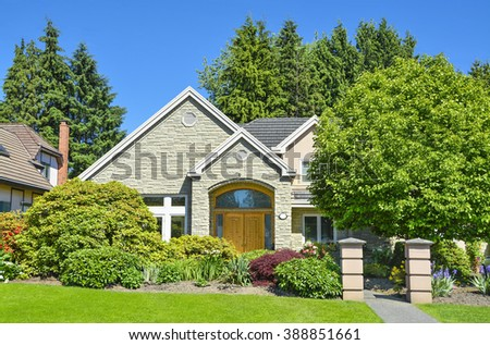 Suburban residential house sinking in green trees and bushes on blue sky background - stock photo