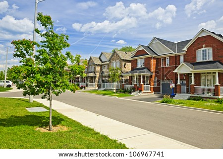 Suburban residential street with red brick houses - stock photo