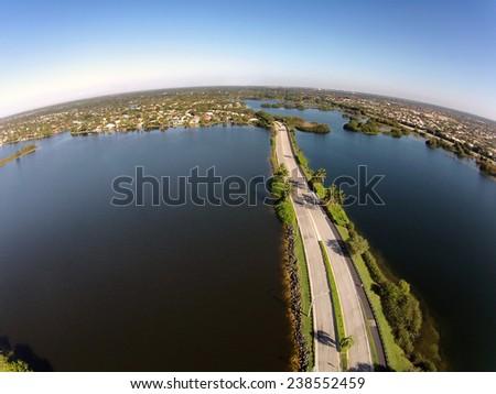 Suburban road crossing lakes in Florida aerial view - stock photo