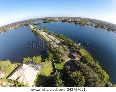 Suburban road in Florida cutting through lakes aerial view - stock photo