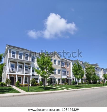 Suburban Three Story Condominiums along Street of Residential Neighborhood sunny blue sky day - stock photo