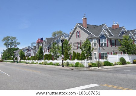 Suburban Three Story Tall Condominium Neighborhood Street American Flag waving in air sunny blue sky day - stock photo