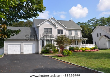 Suburban Two Car Garage Large Siding Home with Double Wide Blacktop Driveway Front Yard on Sunny Blue Sky Cloud Day - stock photo