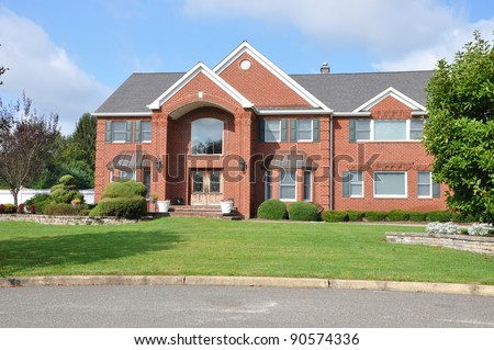 Suburban Two Story Brick Home in residential neighborhood on sunny blue sky day